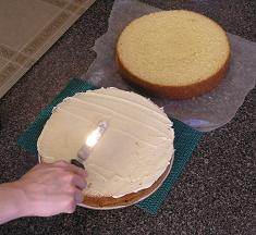 applying butter cream icing on cake image